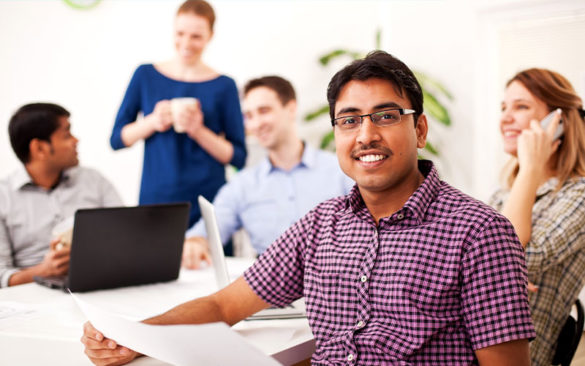 man smiling in an office with a team of people