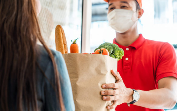 person wearing health mask delivering groceries