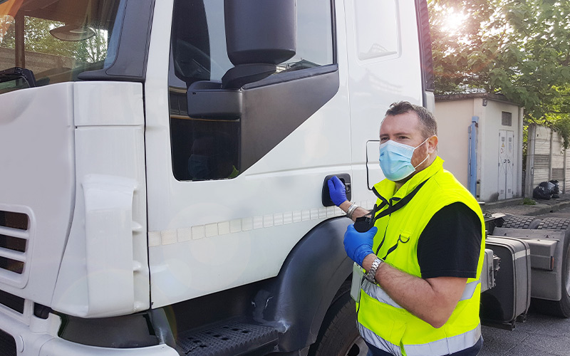 delivery driver with a mask and gloves next to a semi truck