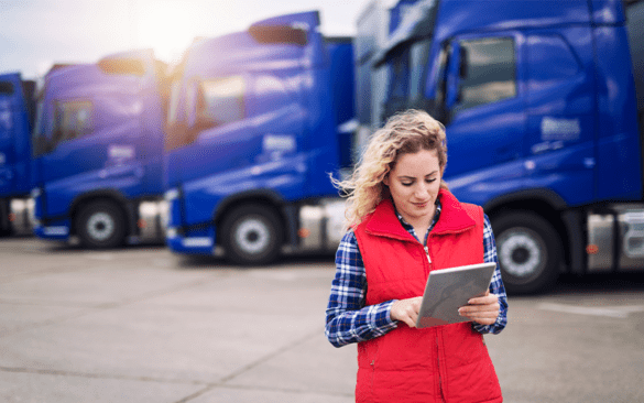 woman using an ipad in front of a row of semi trucks