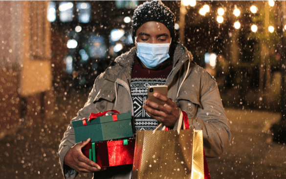 Shopper in the snow holding gifts and looking at a phone